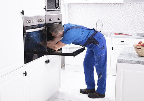 Appliance service technician working on an oven