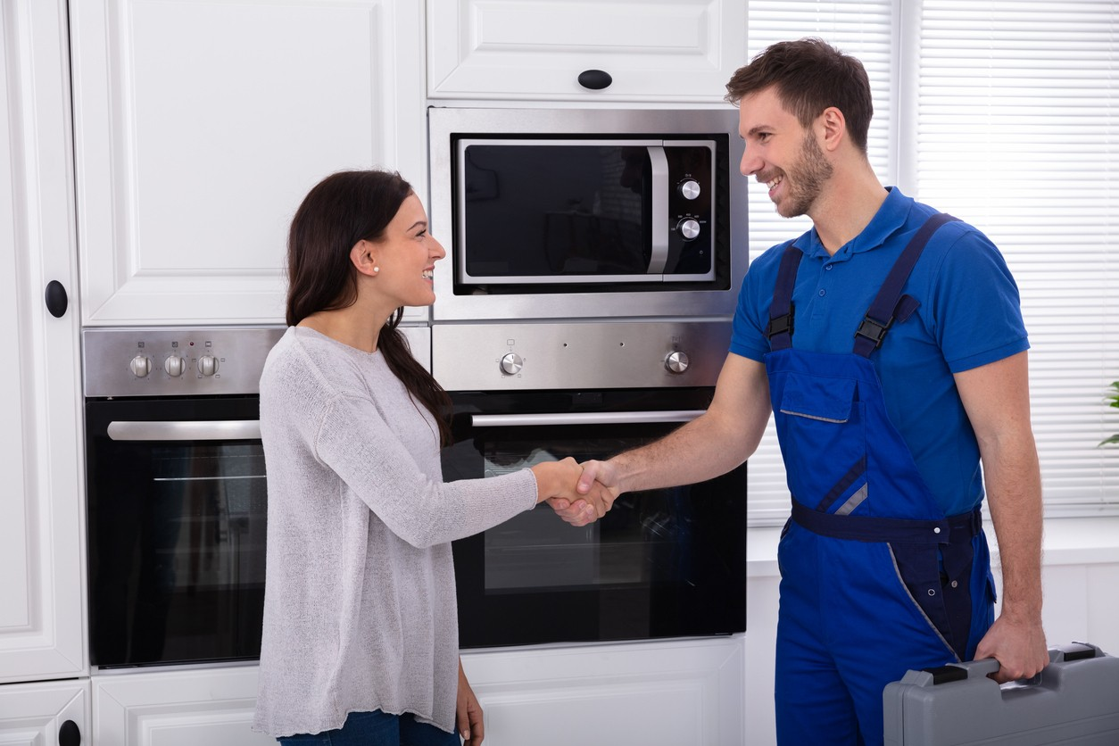 Appliance service technician shaking hands with a local customer following a service visit