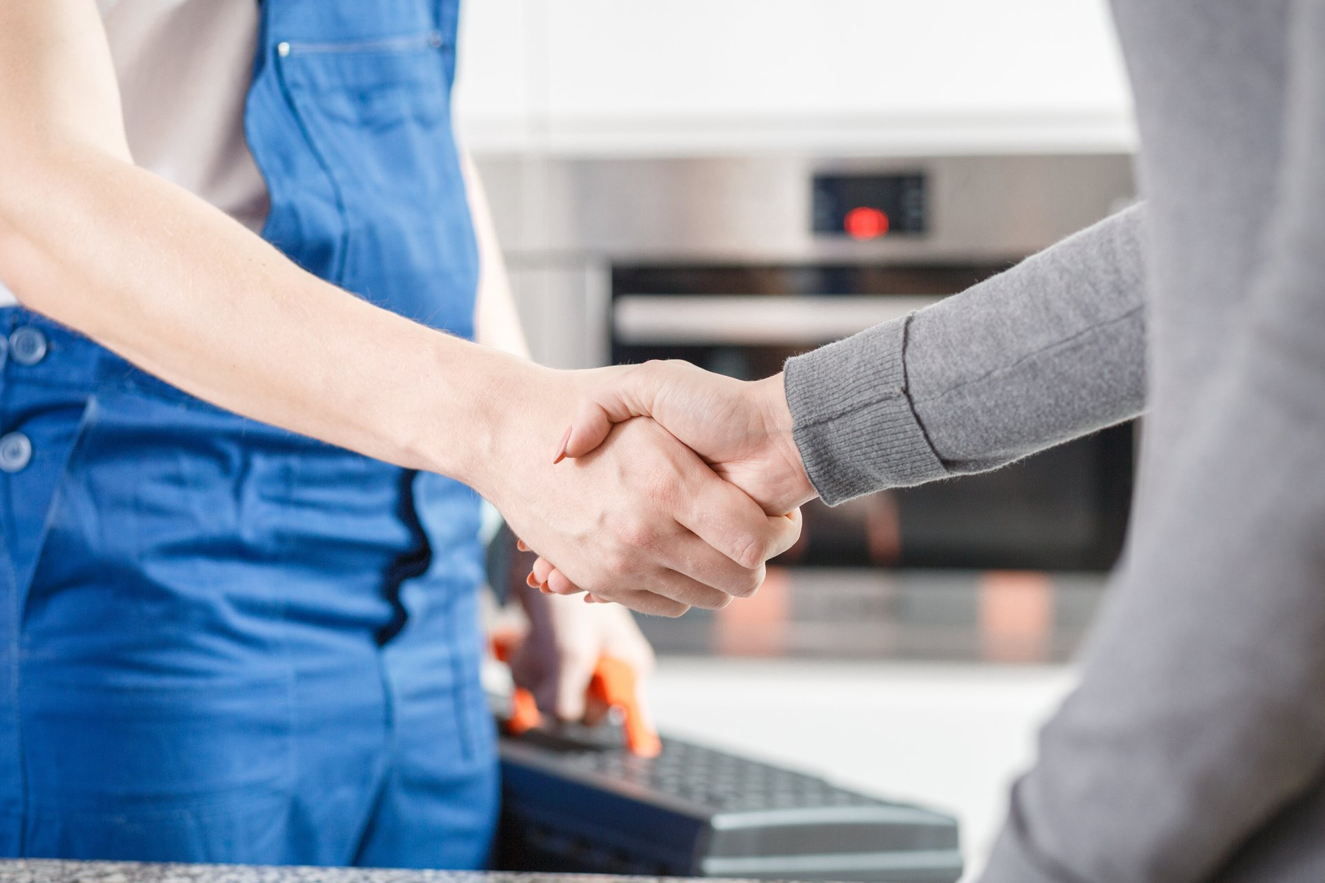 Home service technician shaking hands with customer