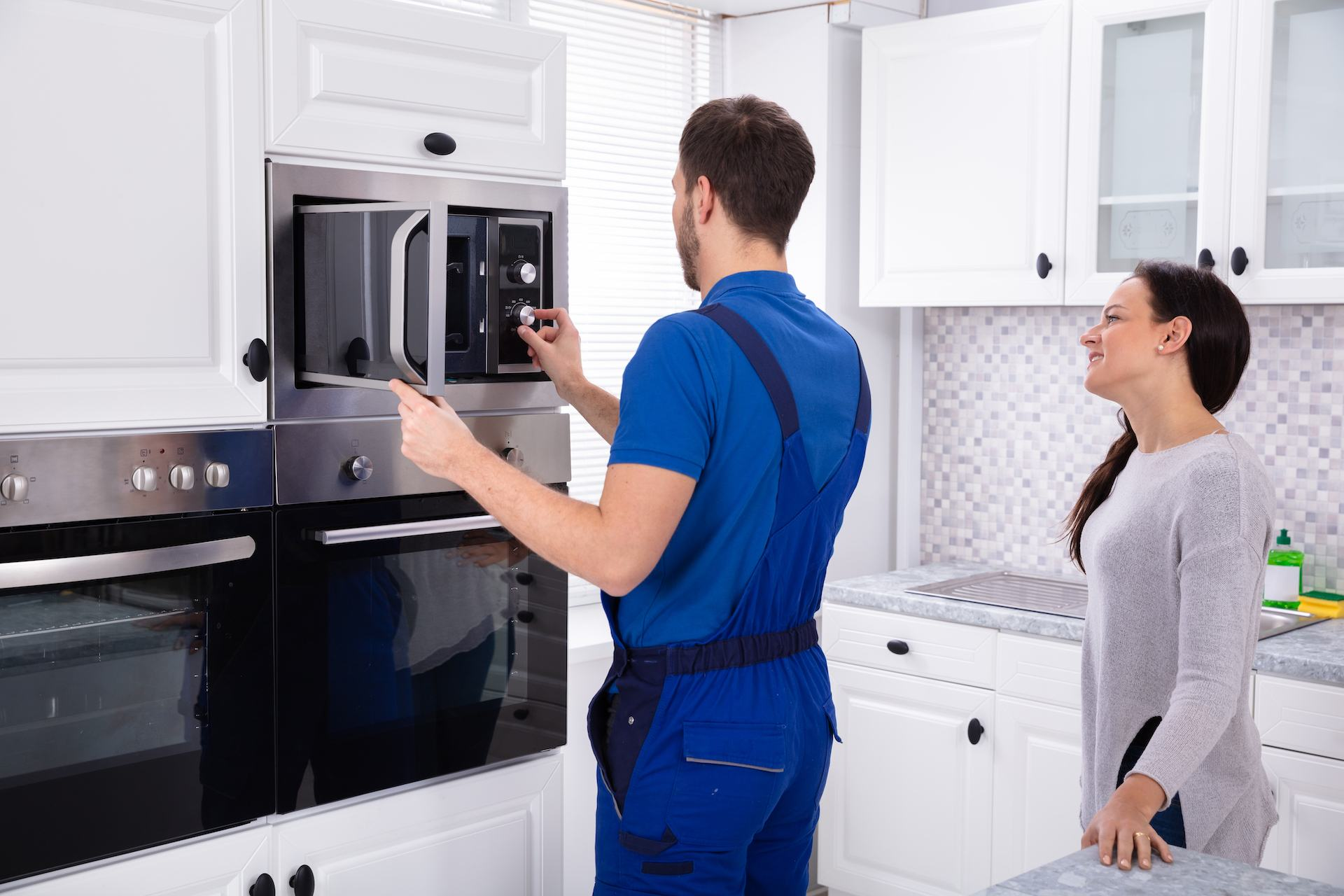 repair technician working on microwave oven