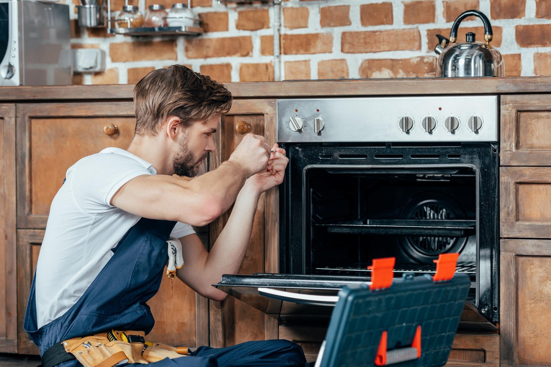 repair man works on range oven