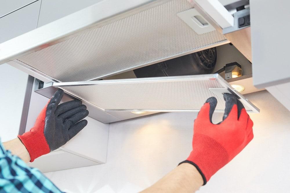 man repairing stove hood